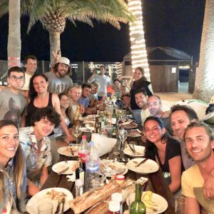 big group of people sitting on a dining table in a surf camp in Corralejo