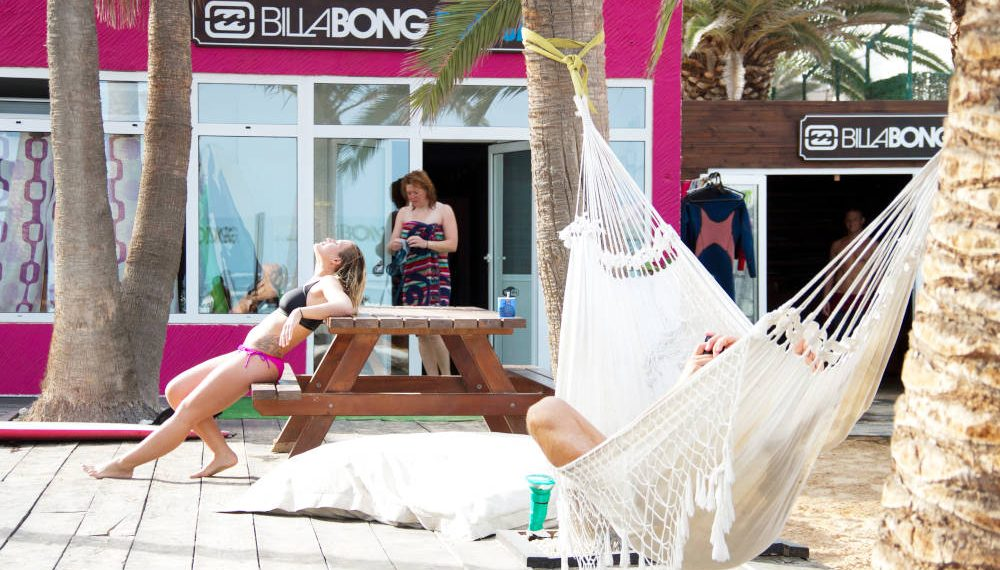 several people relaxing and enjoying the sun on the terrace of a Surfcamp in Corralejo