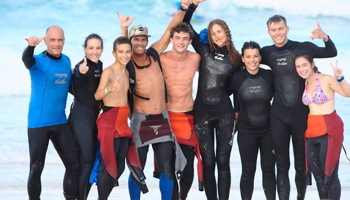 surf school students posing for a picture on the beach in fuerteventura