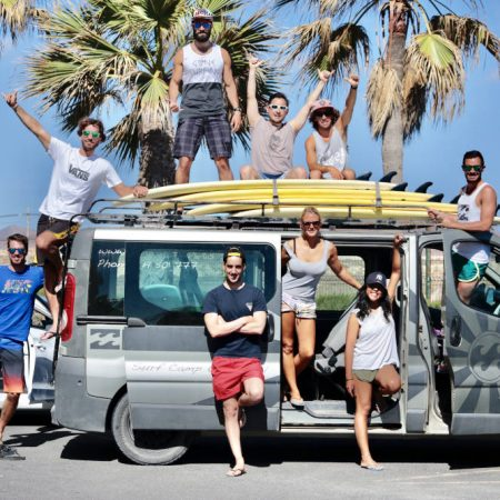 surf school students posing for a picture with the surfboards on the van