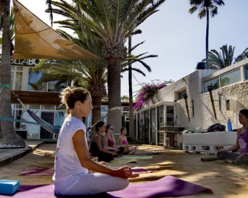 women practicing yoga in on the terrace of the Billabong Surf Camp in Corralejo