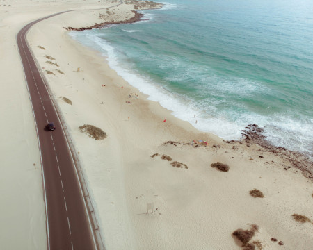 car driving on road along a sandy beach in Fuerteventura