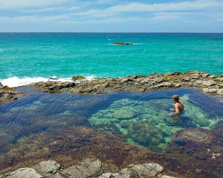 man swimming in the natural pools of Fuerteventura