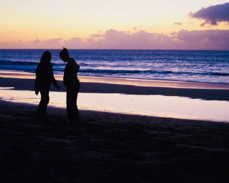 two persons standing on the beach while the sun sets behind the ocean