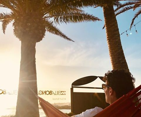 person laying in a hammock while watching sunset in the Billabong Surf Camp in Corralejo Fuerteventura