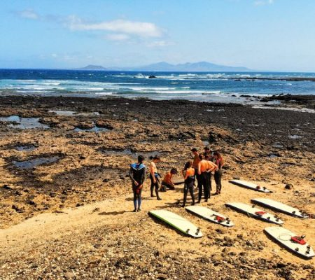 surf school students with surfboards in front of a reef break at Fuerteventura's north shore